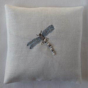 White rough linen cushion embrodered with dragonfly. Dragonfly composed of black thread and glass beads and light fabric wing embroidered with silver thread.