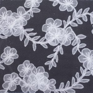 White lace in the pattern of wafting blossom embroidered on a charcoal coloured fabric.
