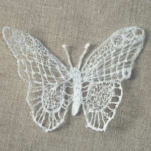 Embroidered lace butterfly in a white thread raised on a light brown linen background.