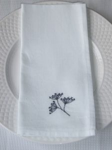 Black threaded embroidered three headed lavender stem on white linen fabric napkin. Napkin is resting on traditional white dining plate.